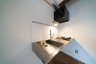 壁がメトロタイル貼りのステンレスキッチン。