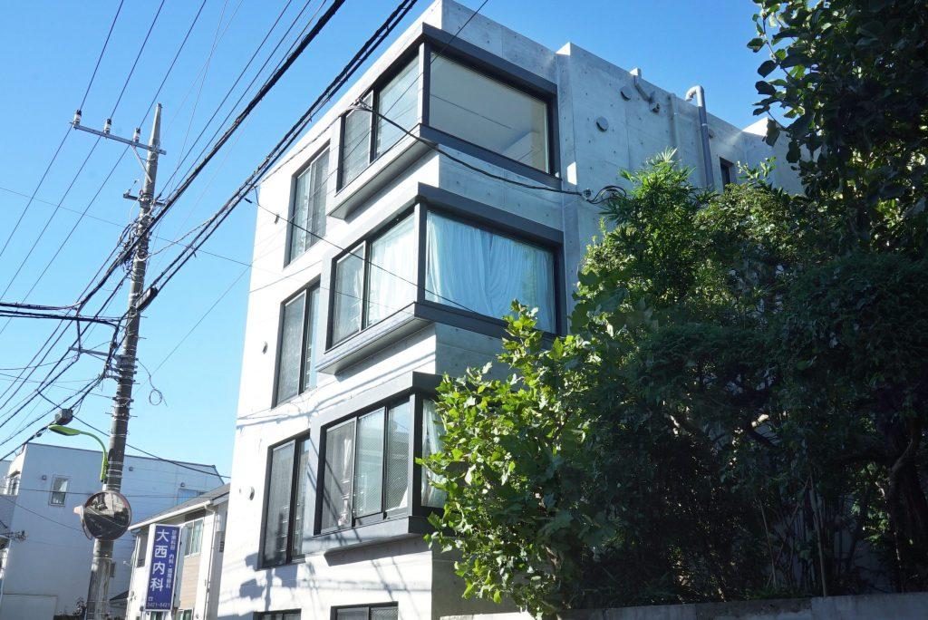 青空に映えるシンプルな外観のマンションです。