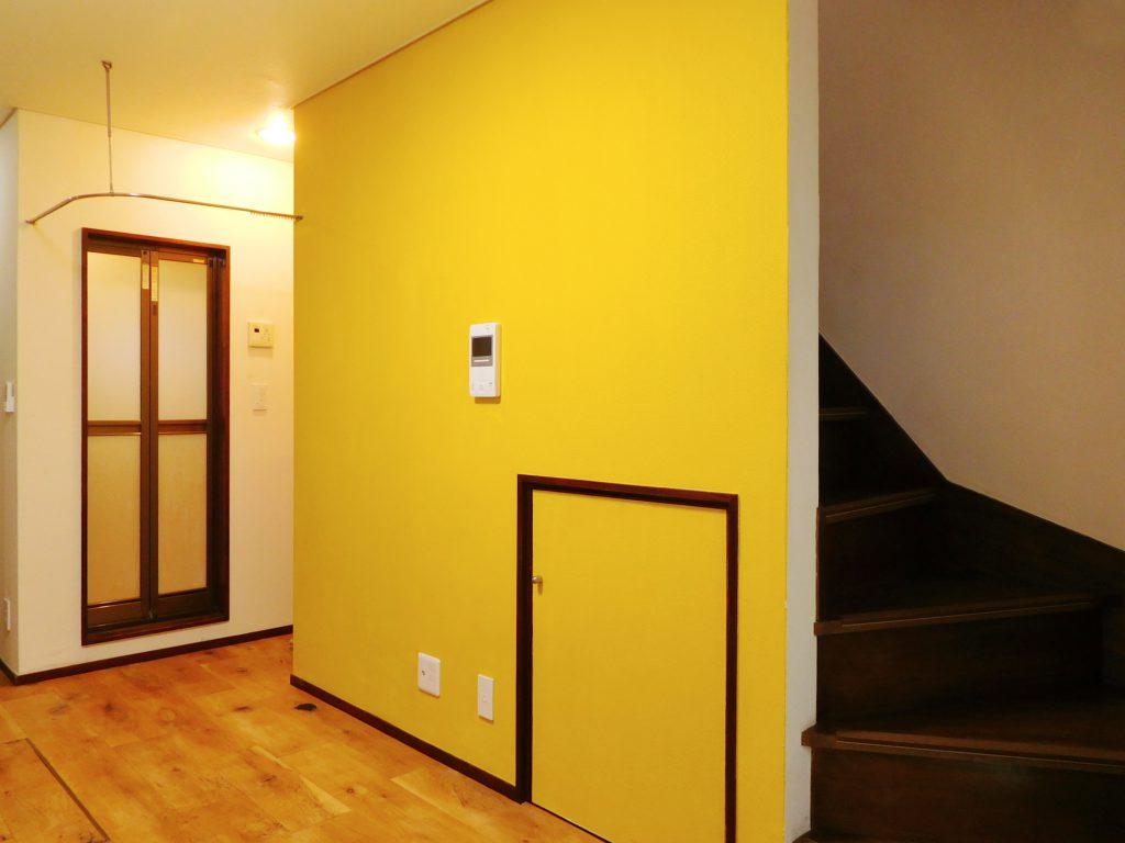 クロームイエローの壁がお部屋の象徴。この壁の後ろには2階への階段があります。
