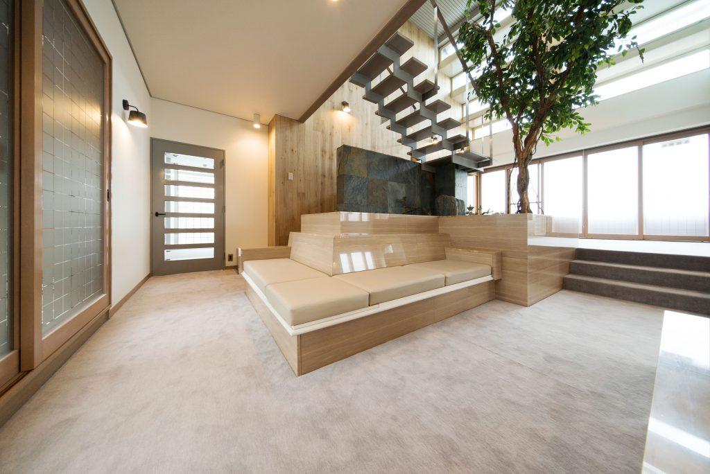 階段下にはソファーとフェイクグリーンの木が。