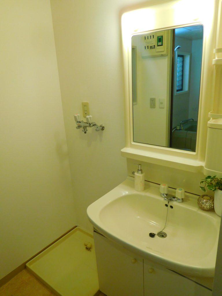 独立洗面台の鏡の前に小さなカウンターがあると小物が置けてさりげなく便利です