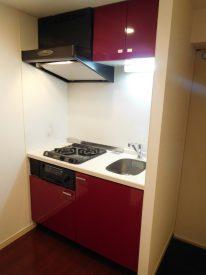 床材に合わせた赤がかわいいキッチン