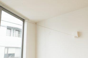洗濯物は部屋内にある、使いたい時だけ伸ばして使うワイヤータイプのもの。