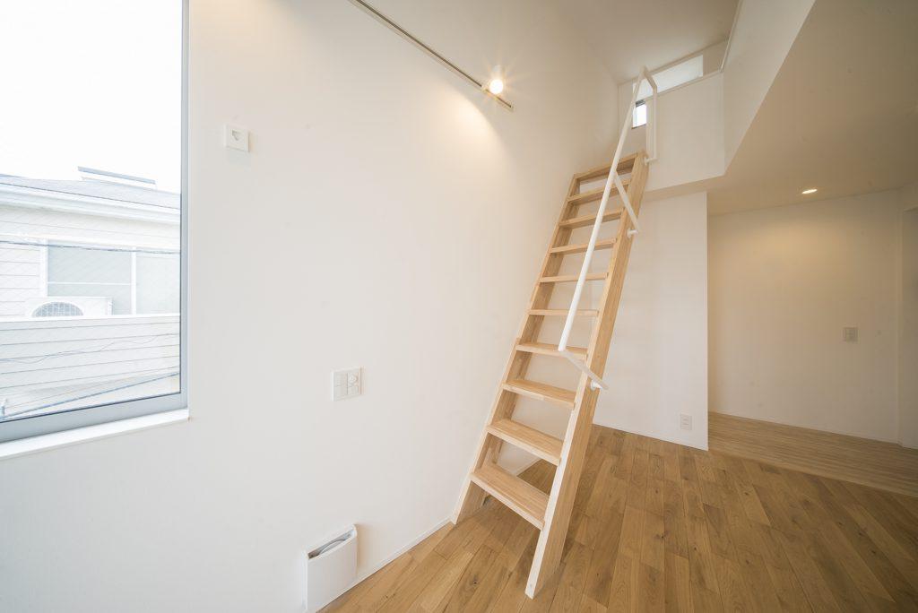 洋室の中央にあるロフトへの階段。木製で、内装と調和しています。