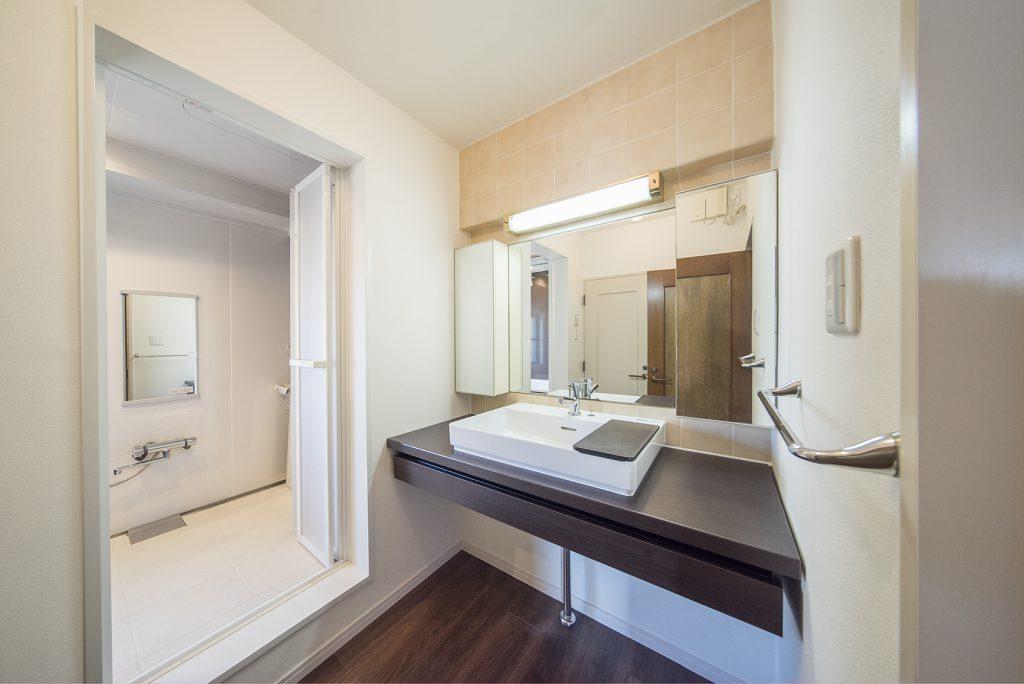 大きな鏡、天板に洗面ボウルを乗せた粋なデザインの洗面台。