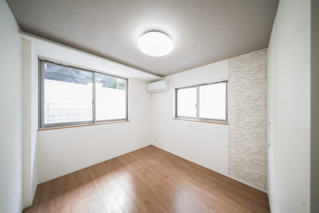 窓側はベッドとフロアライトだけ置いた寝室に。