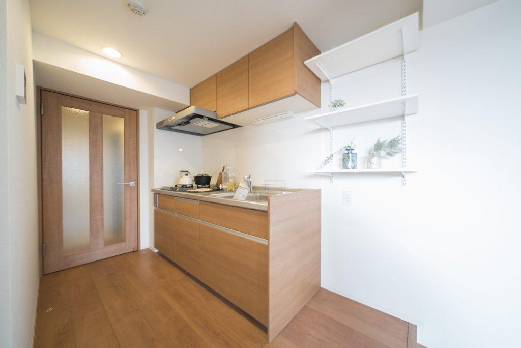 キッチンは洋室から一段上がって。ブラウンのデザインがナチュラルでいい。