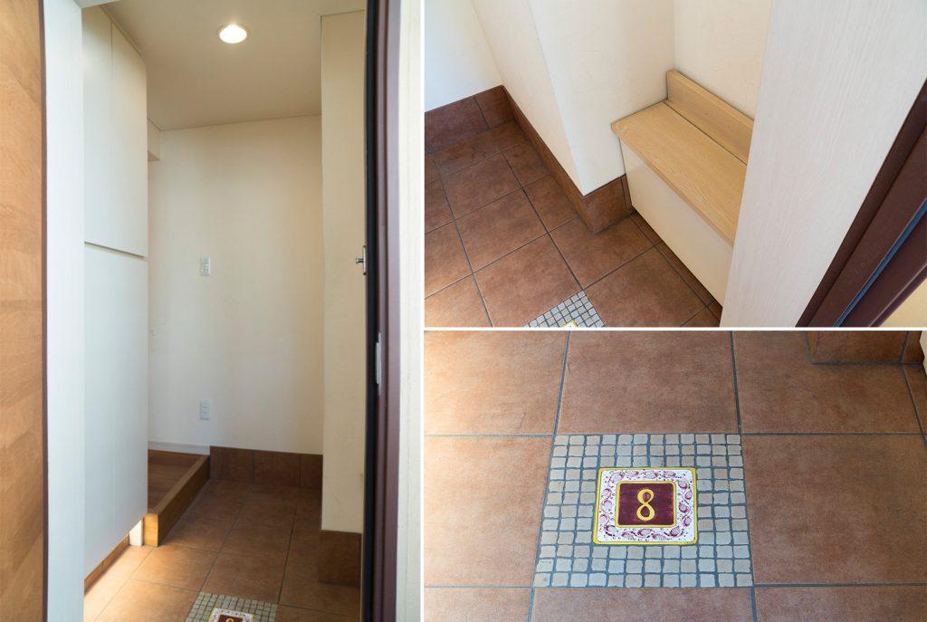 小さなベンチのある玄関。足元には部屋番号のタイル。