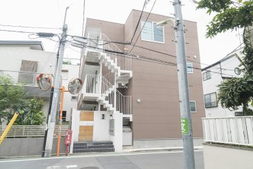 木製のオートロック扉がお出迎え。住宅街に建つ3階建てのアパートです。