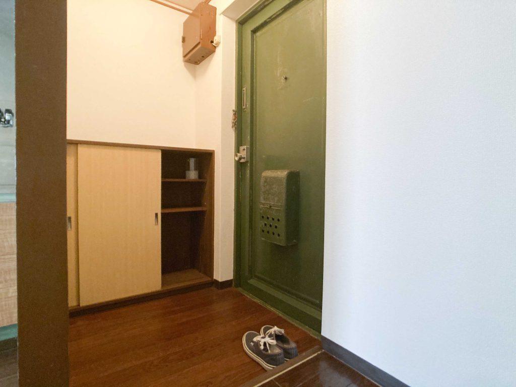 玄関。ドアがグリーン。下駄箱ついてます。